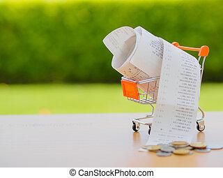 carro de compras, con, receiptwith, coins, en, tabla de madera