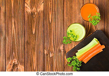 Carrot and celery juice in glasses with cut fresh vegetables and green parsley leaves on kitchen board with copy space.