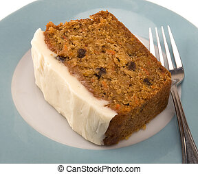 piece of carrot cake with cream cheese icing on turquoise plate