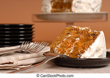 A piece of carrot cake with forks, plates, and whole cake in background