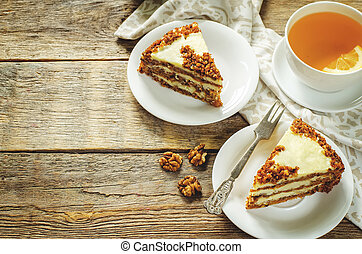 carrot cake with raisins, walnuts and butter cream on a dark...