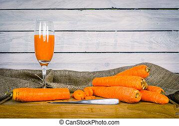 Carrot juice on a wooden board