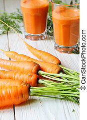 carrot on the table and two glasses of juice