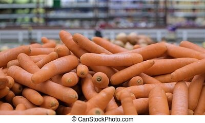 carrots by weight at the grocery store. The camera moves along the vegetables
