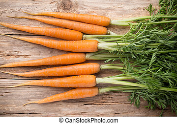 Carrots. - Carrots more on a wooden background. Studio...