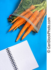 carrots with leaves and notebook on blue background