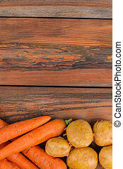 Carrots with potatoes on wood with copyspace.