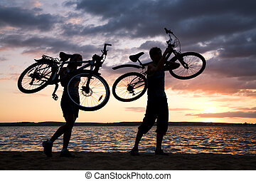 Carrying bikes - Silhouettes of couple carrying their bikes...