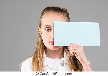 Cute long-haired little lady with blue eyes holding empty paper