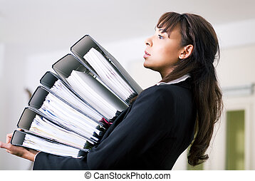 Carrying files - Female office worker carrying a stack of...