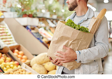 Carrying full paper bag at food market