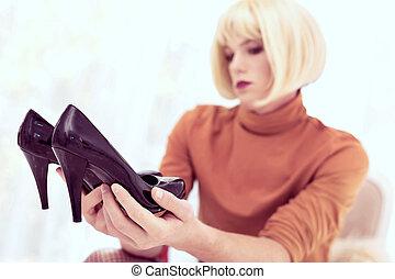 Transgender man in light wig regarding black high heels