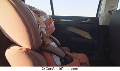 Carrying little girl passenger in car child forward-facing seat with harness