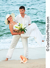 Carrying  - man carrying woman on the tropical beach