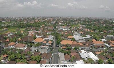 Cars and bikes on the road in Canggu city Bali island 4K Drone flight