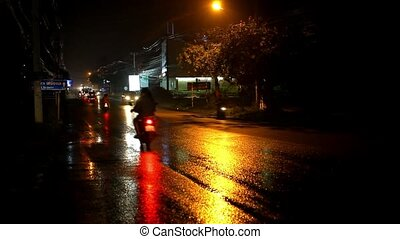 Cars and motorbikes driving on a wet road at night after rain. Video