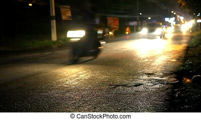 Cars and motorbikes driving on a wet road at night after rain.