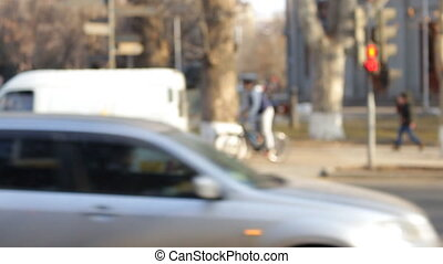 Cars and people out of focus in front of the camera, traffic light