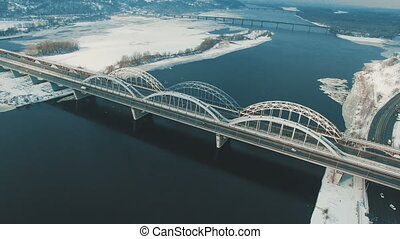 Cars and train moves on a bridge over a frozen river aerial drone footage