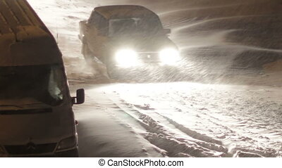 Cars are going in the Night in Winter on Snow-Covered Roads.