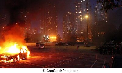 Car involved in flames with highrises and SWAT officers standing by