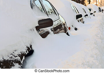 Row of cars covered by deep snow. Urban street after the heavy snowstorm.