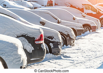 Cars covered in snow on a parking lot in the residential area.