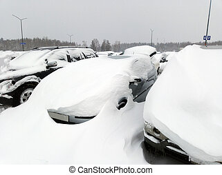 Cars covered in snow on a parking lot in the residential area during snowfall.