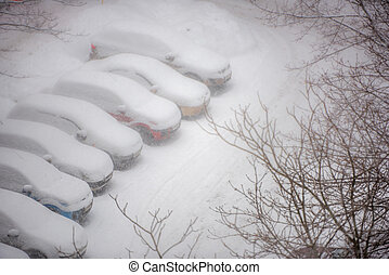 Cars covered in snow on a parking lot in the residential area du