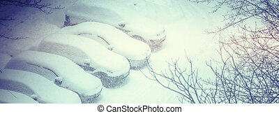 Cars covered in snow on a parking lot in the residential area during snowfall