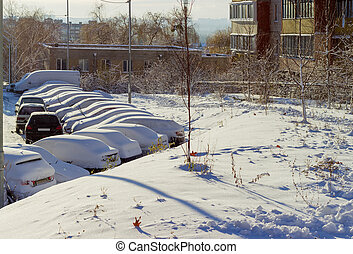 Cars covered with snow on parking lot in residential area