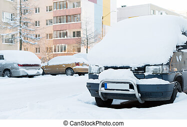 Cars covered with snow on the street in winter.