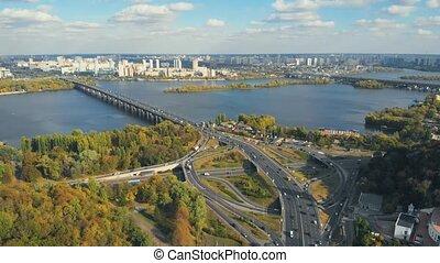 Cars crossing bridge interchange overpass. Highway interchange with traffic. Aerial highway. Expressway. Road junction. Car in motion. Bridge with traffic. Aerial view of the vehicular intersection.