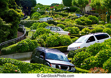 SAN FRANCISCO - MAY 20 2015:Cars drive down Lombard Street switchback. Lombard Street is known for the one-way block on Russian Hill where 8 sharp turns make it the most crooked street in the world.