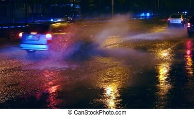 Cars drive into large puddles on the night road in the city, spray puddles scatter from under the wheels of the car
