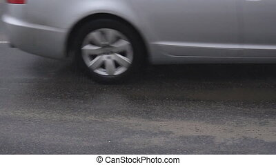 Cars drive on dirty and wet asphalt with reagents, slow...