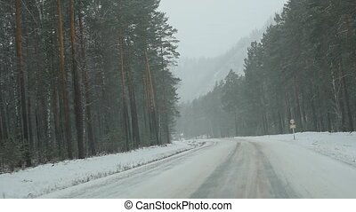 Cars drive through forest In snowstorm. view through the windshield. slow motion