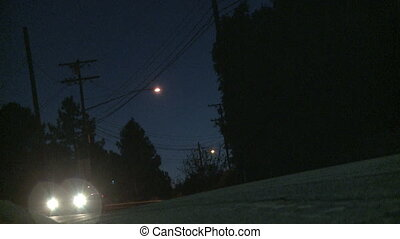 Cars driving by at twilight on a mountain road near Los Angeles in the Hills