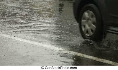 Cars driving by rainy city street