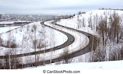 Cars driving on snowy road in winter, traffic driving along freeway highway