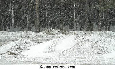 Cars driving on suburban road on snowy winter day