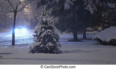 Cars driving slowly, snow covered street in a residential area at night
