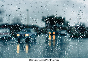 Cars driving through heavy rain; raindrops on the windshield