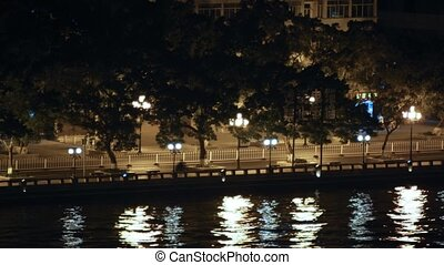 Cars go along embankment of Pearl river at night in light of lanterns