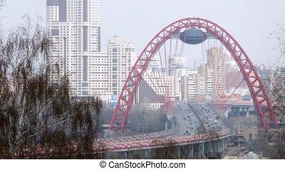Cars go on bridge against city landscape, time lapse
