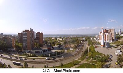 Cars go on highway against city landscape of Samara in sunny day, time lapse