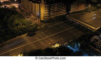 Cars go on night street on backbone under foot bridge
