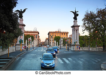 Cars go on Ponte Vittorio Emanuele II in Rome, Italy, beautiful sculptures