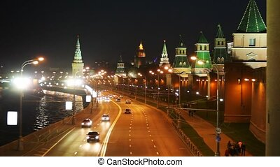 Cars go on road along the river and Kremlin towers in Moscow