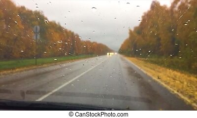 cars go on the road asphalt. autumn beautiful view forest, raindrops on the glass car blurred background travel slow motion video